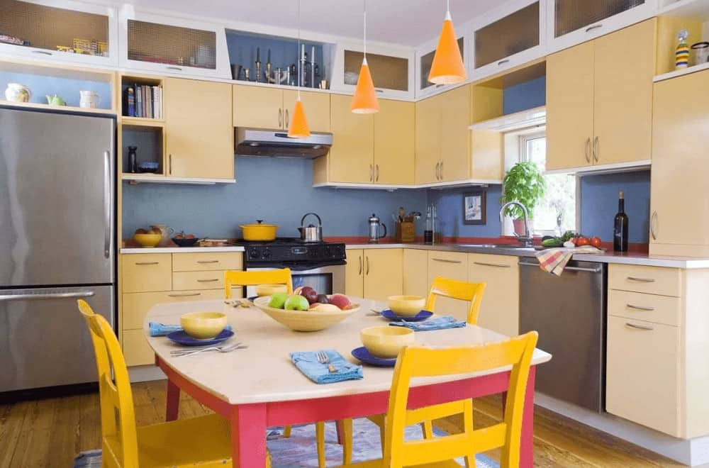 Brightly colored dining set lighted by cone pendants brings a cheerful tone in this kitchen with stainless steel appliances and light yellow cabinetry against the blue walls.