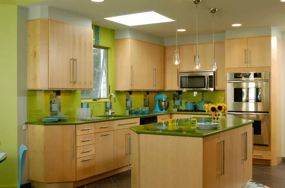Sleek kitchen with light wood cabinetry and a matching breakfast island topped with a green counter that complements the high gloss backsplash tiles. It is illuminated by glass pendants and recessed ceiling lights.
