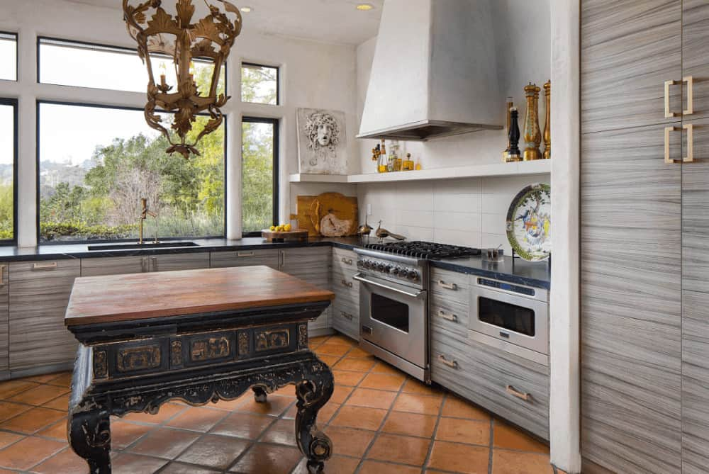 Eclectic kitchen with terracotta flooring and glass-paneled windows overlooking the outdoor greenery. It includes a white range hood and a carved kitchen island illuminated by an eccentric chandelier.