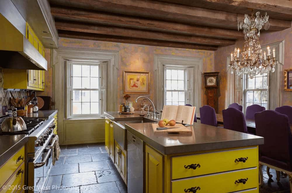 An eat-in kitchen offers yellow cabinetry and a matching island bar fitted with ornate wrought iron hardware and a vessel sink. It has brick flooring and wood beam ceiling mounted with a fancy candle chandelier.