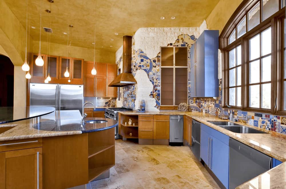 Marvelous kitchen with limestone flooring and artistic wall showcasing white bricks dominated by decorative backsplash tiles. It includes wooden framed windows and a stylish island bar illuminated by glass pendant lights.