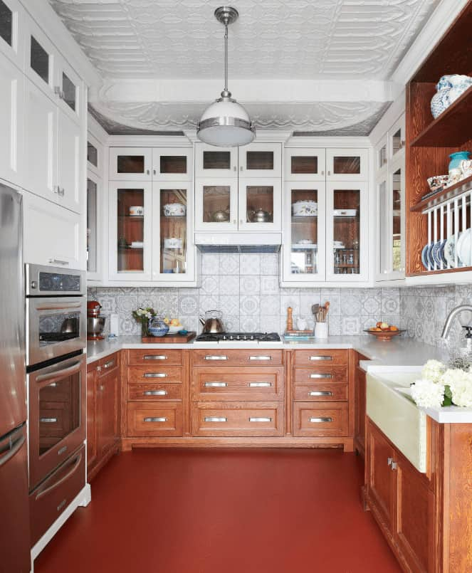 A chrome dome pendant light that hung from the ornate white ceiling illuminates this kitchen boasting wooden lower cabinets and glass front upper cabinets accented with decorative backsplash tiles.