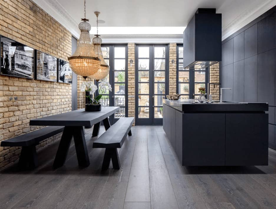 This kitchen is decorated with fabulous chandeliers and a photo gallery mounted on the brick wall. It has sleek black cabinetry and island with modern vent hood on top along with a dining table flanked by matching benches.