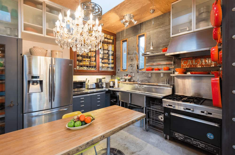 Eclectic kitchen boasts black cabinetry and stainless steel appliances complementing with the countertops and dual sink. There's a rectangular table in the middle lighted by a fancy chandelier.