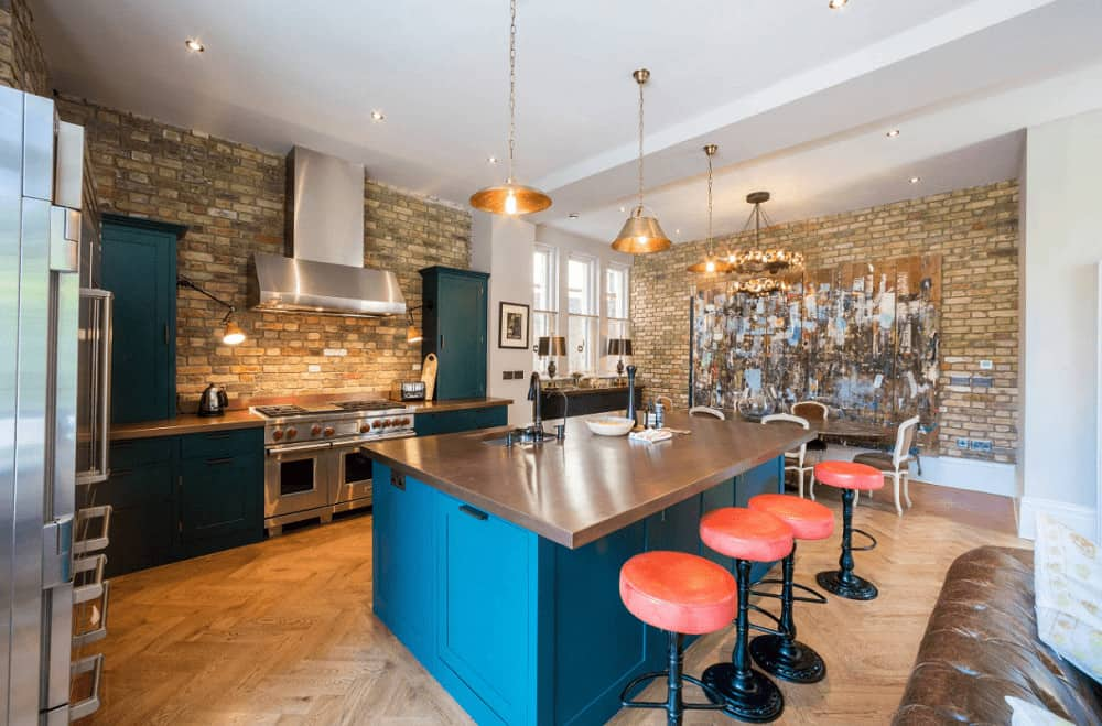 Stone brick walls mounted with multi-panel artwork and a stainless steel range hood add texture in this kitchen with blue cabinetry and a matching breakfast island lined with orange bar stools.