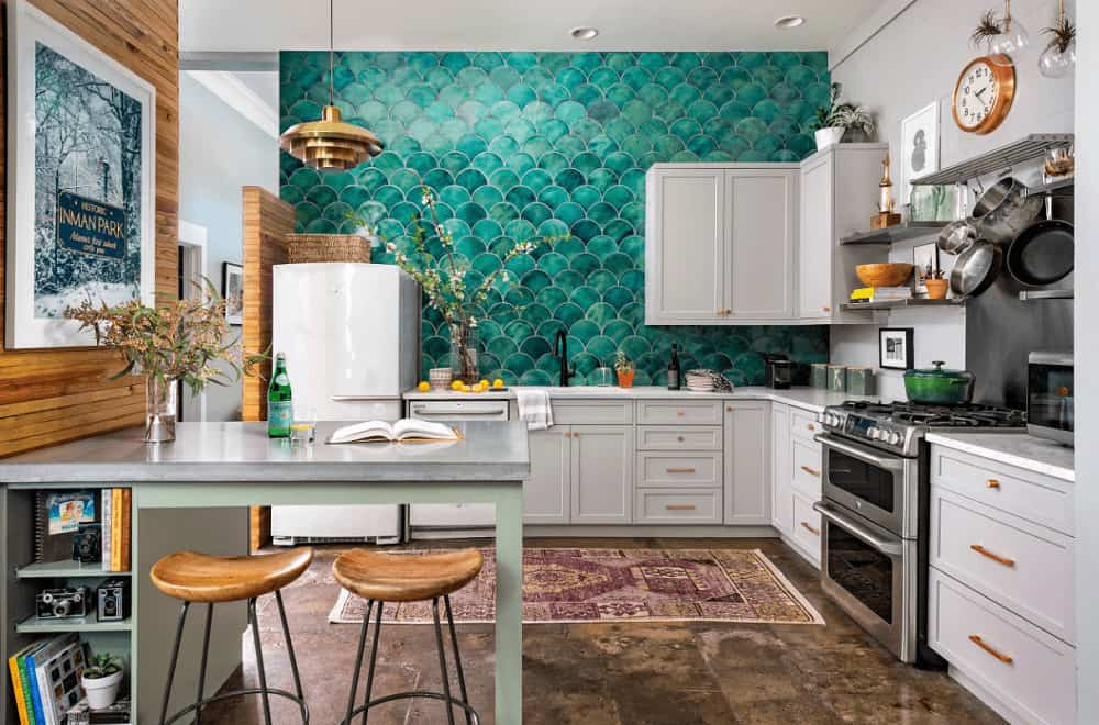 A green patterned wall sets a gorgeous backdrop to the white cabinetry accented with copper hardware. This kitchen is decorated with a round wall clock and a white framed artwork mounted on the wood-paneled wall.