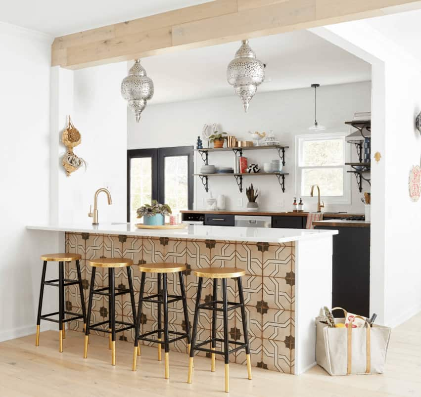 A pair of unique chrome pendants hang over the white peninsula clad in decorative tiles. It is contrasted by black stools with gold seats along with charcoal cabinetry topped with wooden counters.