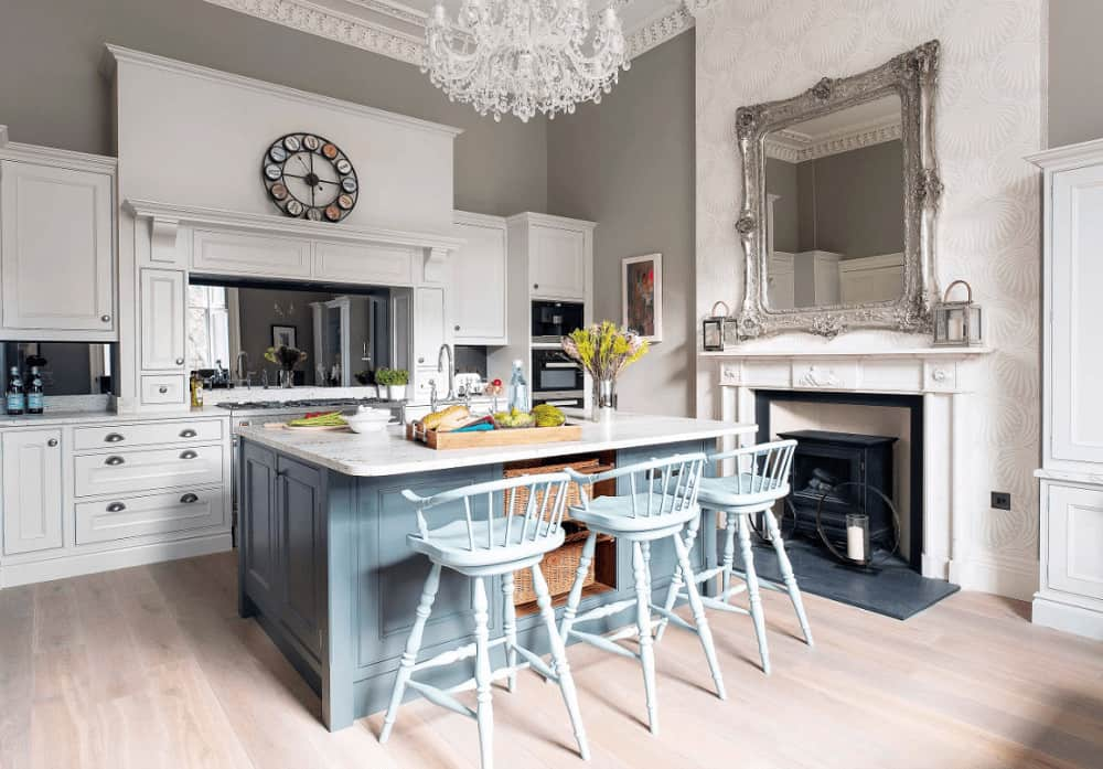 A gorgeous mirror hangs above the fireplace facing the blue center island that's lined with wooden counter chairs. This kitchen has a fancy crystal chandelier and white cabinetry with a smoke mirrored backsplash.