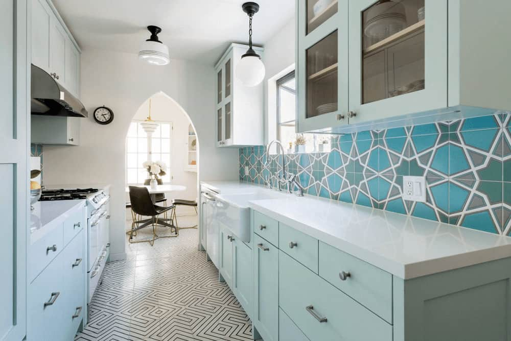 Eye-catching blue backsplash tiles add a stunning accent in this kitchen with muted green cabinetry and a white vessel sink paired with chrome fixtures. It has striking tiled flooring and an arched doorway leading out to the dining area.