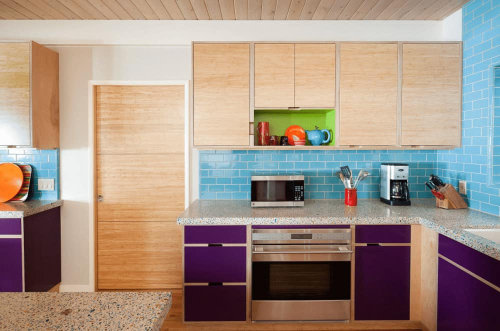 Eclectic kitchen showcases blue subway backsplash tiles and violet lower cabinets topped with granite counters. It has a wood plank ceiling and light hardwood flooring that complements the wooden door and upper cabinets.