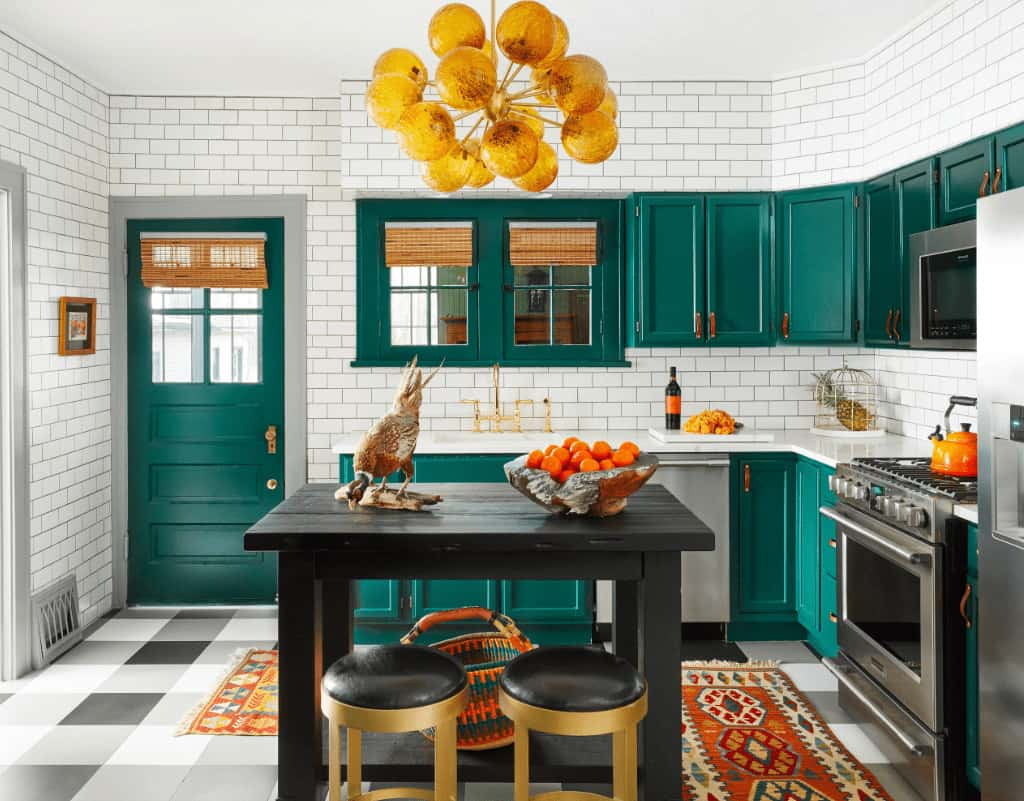 A contemporary chandelier hangs over the black kitchen island paired with cushioned bar stools. This kitchen boasts stainless steel appliances along with emerald green cabinetry and door that stands out against the white subway backsplash tiles.