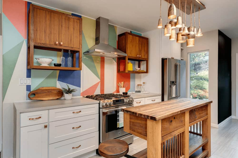 Gorgeous kitchen with tiled flooring and multi-colored walls mounted with floating cabinets and a stainless steel range hood. It includes white cabinetry with copper pulls and a wooden island bar lighted by vintage pendants.