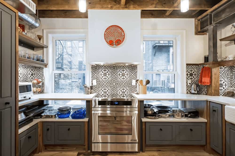 A pair of glass pendants that hung from the wood beam ceiling illuminate this kitchen showcasing gray cabinetry and decorative backsplash tiles that are fixed above the white quartz countertops.