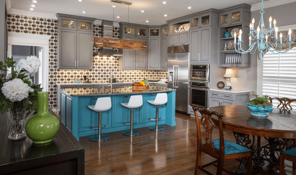 Gorgeous kitchen with natural hardwood flooring and regular white ceiling mounted with recessed lights and a lovely candle chandelier. It includes gray cabinetry and a blue island bar lined with white counter chairs.