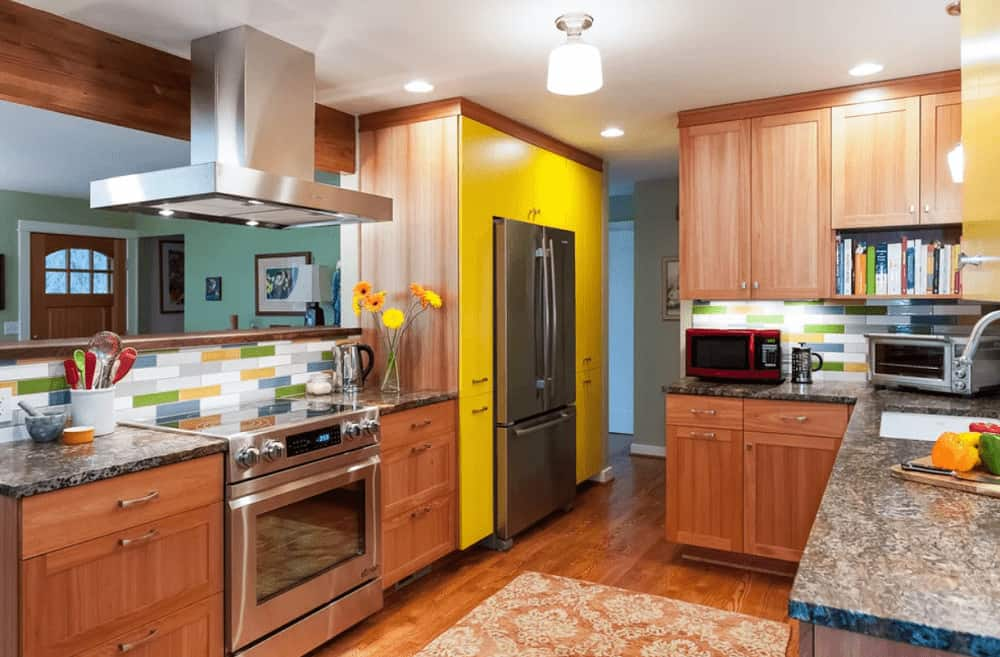 The cozy kitchen offers stainless steel appliances and wooden cabinetry that blends in with the hardwood flooring topped by a vintage rug. It is illuminated by a glass semi-flush mount light and recessed ceiling lights.