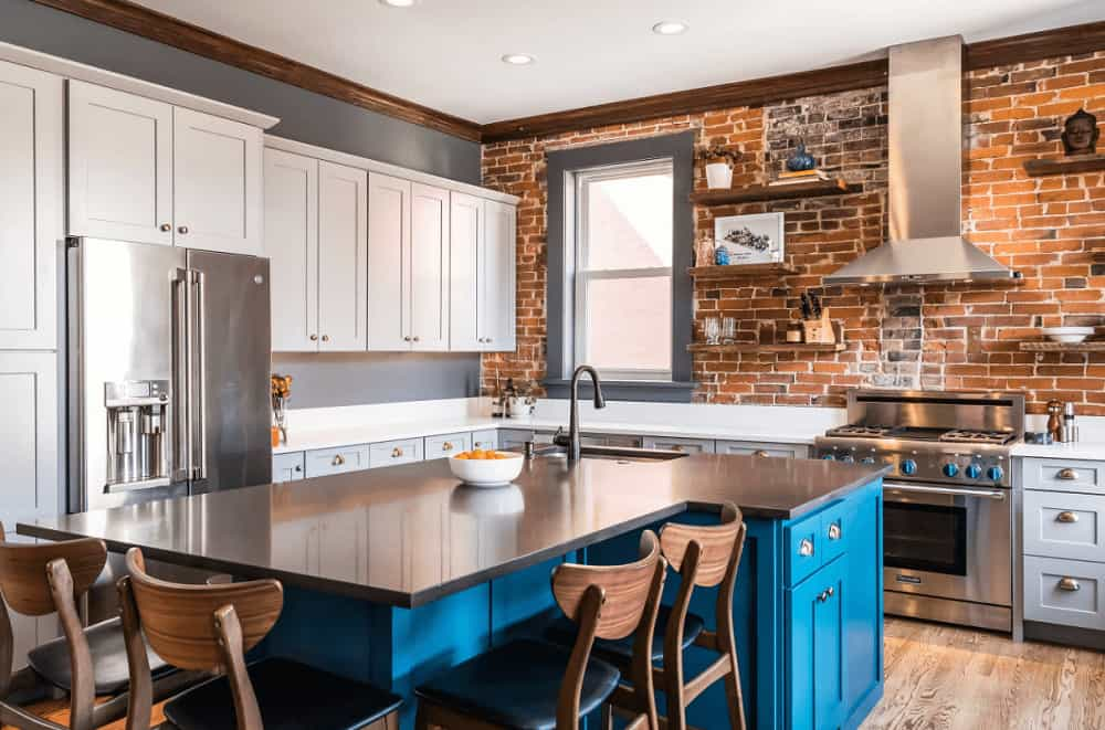 Black cushioned chairs sit at a blue breakfast island that's fitted with storage and sink. This kitchen has white cabinetry and wooden floating shelves fixed on the distressed brick backsplash.