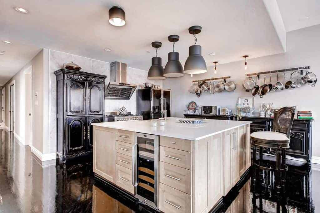 This kitchen features a large center island with a built-in storage and wine fridge illuminated by dome pendant lights. It includes a cushioned chair and black cabinetry that complements the high gloss flooring.