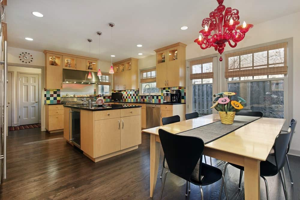 Multi-colored backsplash tiles bring a pop of color in this eat-in kitchen with light wood cabinetry and matching breakfast island across the dining space lighted by a red chandelier. It has natural hardwood flooring and white framed windows covered in wicker roman shades.