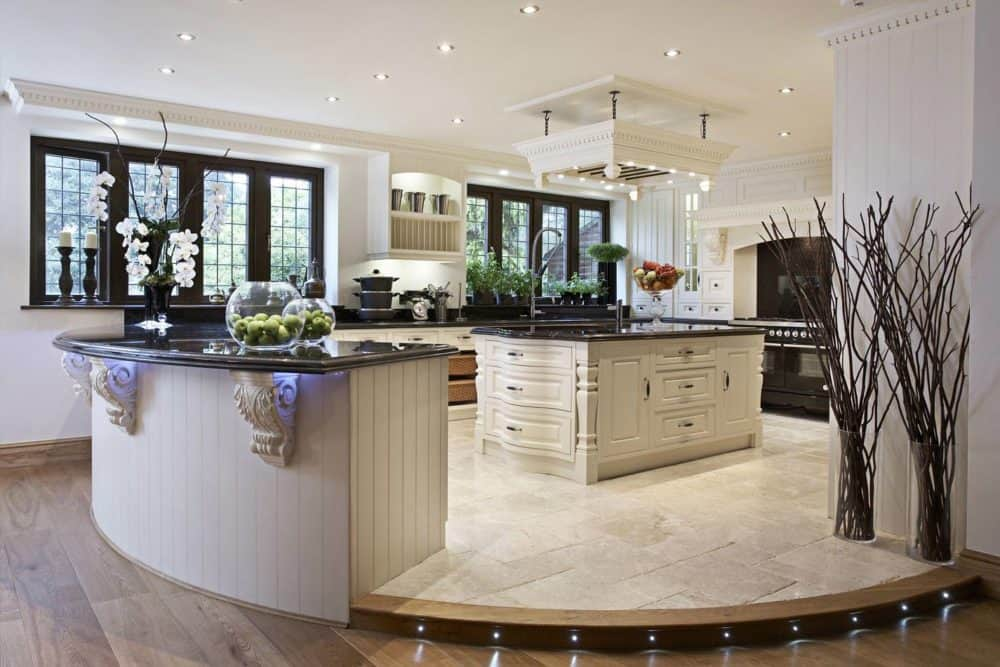 Well-lit kitchen showcases a white central island under a pot rack surrounded by matching cabinetry and a curved peninsula with a beadboard base. It sits on a platform clad in limestone flooring.