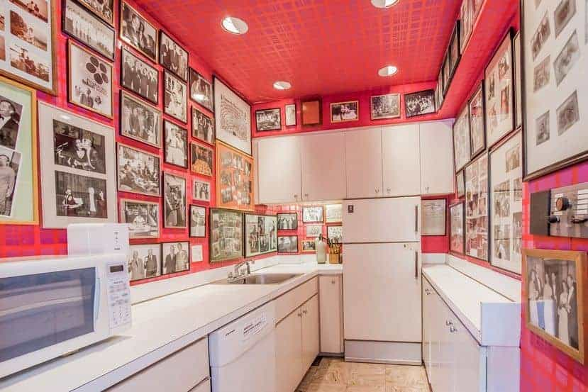 Small kitchen with white appliances and cabinetry illuminated by recessed ceiling lights. It is surrounded by pink walls that are filled with black and white photo gallery.