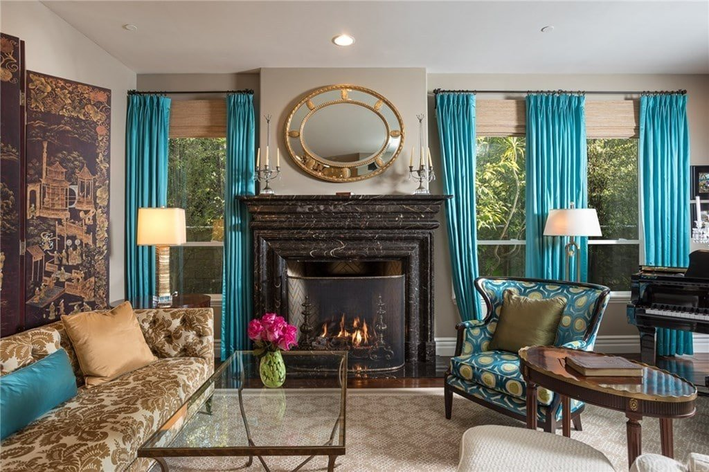 A stylish round mirror hangs above the marble fireplace that's enclosed in a metal screen. This living room offers mismatched seats and a glass top table on a beige patterned rug along with glass paneled windows that are dressed in wicker roman shades and turquoise blue draperies.