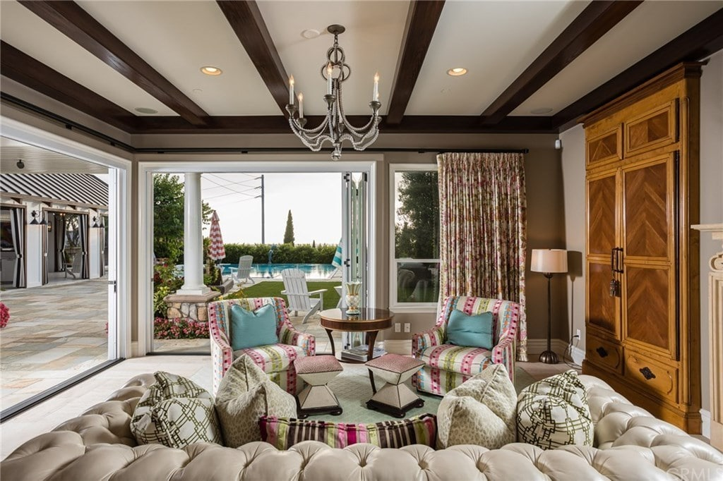An eclectic living room with a view of the sparkling pool showcases a chesterfield sofa and charming patterned chairs paired with matching ottomans. It is illuminated by recessed lights and a candle chandelier that hung from the wood beam ceiling.