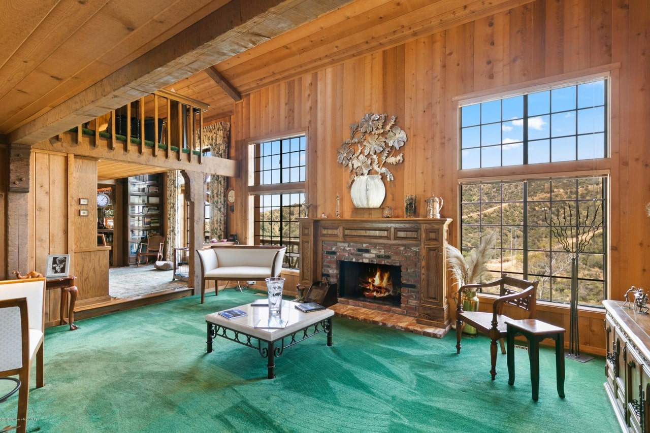 Clad in light wood planks, this cozy living room boasts wooden seats and a granite top coffee table facing the brick fireplace that's accented with a flower vase wall art. It has green carpet flooring and aluminum framed windows overlooking the outdoor scenery.