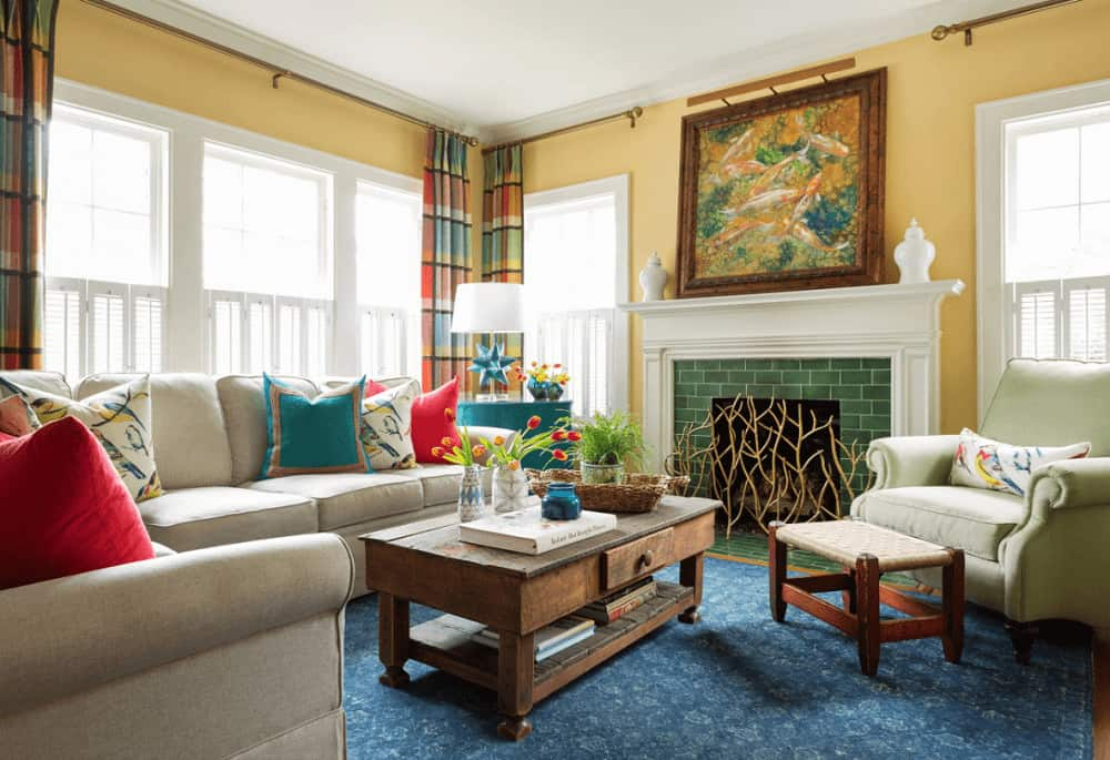 Lovely plaid curtains bring a pop of colors to the white framed windows in this living room featuring beige seats and a green brick fireplace with a koi fish painting on top.