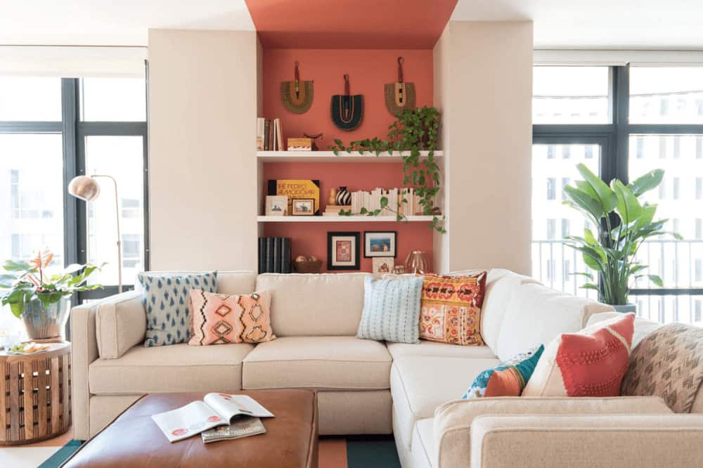 Various styled pillows and red built-in shelving add a pop of colors in this eclectic living room featuring an L-shaped sectional paired with a brown leather ottoman.