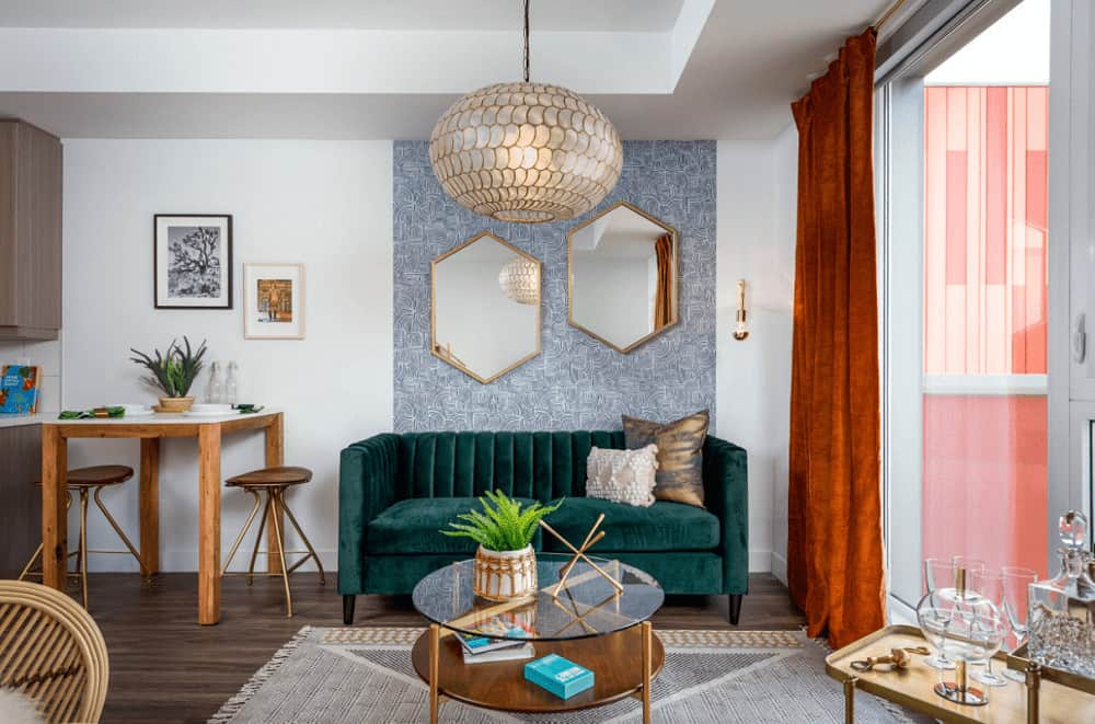 Fabulous living room decorated with hexagonal mirrors and a round pendant light that hung over the glass top coffee table. It has a green velvet seat and classic red draperies covering the full height window.