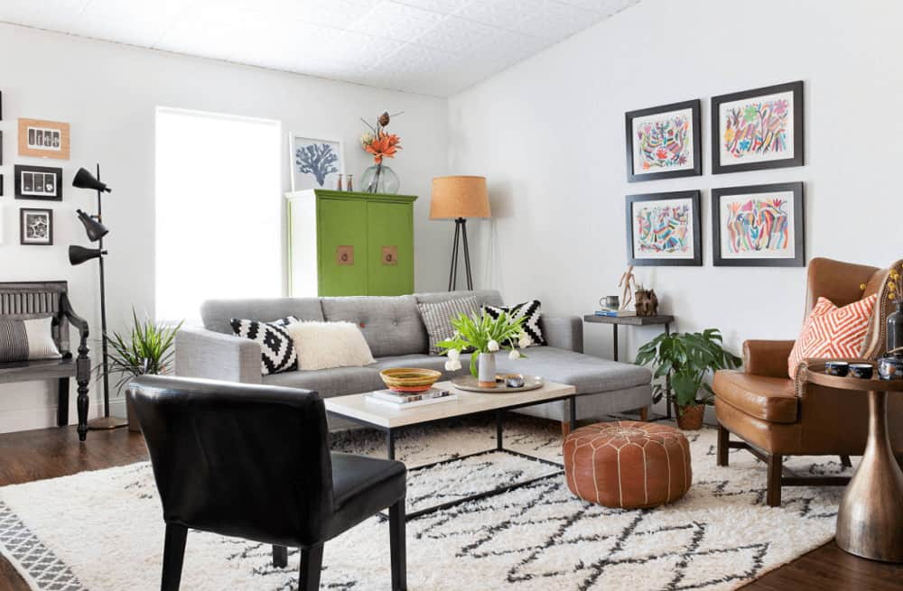 Small potted plants create a refreshing ambiance in this living room with mismatched seats and a green storage cabinet that stands out against the white walls.