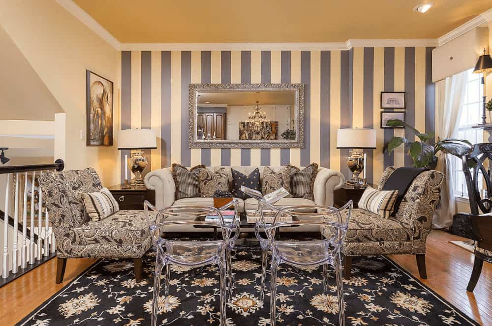 Eclectic living room boasts fabric and glass seats surrounding a black coffee table over a black floral rug. It includes drum table lamps and a gorgeous mirror mounted on the striped accent wall.
