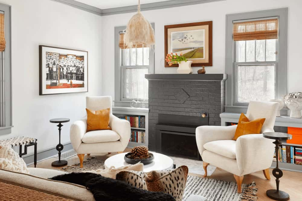 A unique pendant light hangs over the round coffee table that's surrounded with gray sofa and sleek white chairs accented with amber pillows.