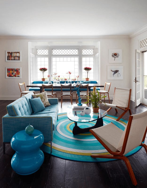 A glass top coffee table sits on a round area rug over wide plank flooring. It is accompanied by beige chairs and a blue tufted sofa with a high gloss sleek table on the side.