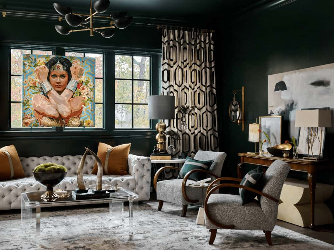 A gorgeous portrait stands out in this black living room with gray armchairs and a chesterfield sofa paired with a glass coffee table. It includes a contemporary chandelier and wooden console table topped with a sleek table lamp and framed photos.