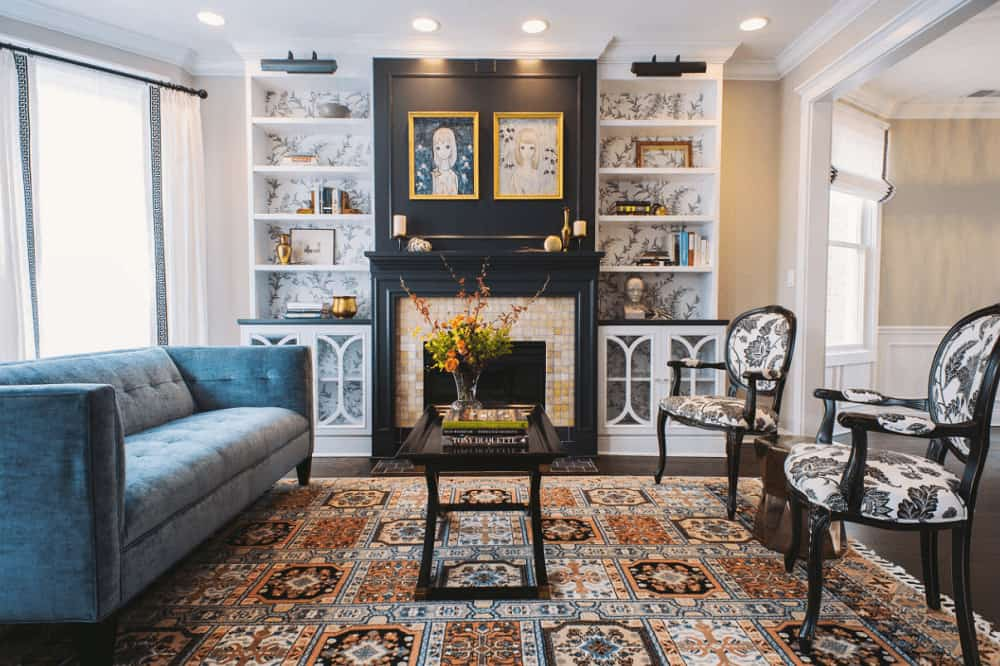 A velvet tufted sofa faces the black coffee table and round back chairs in this living room with an eye-catching patterned rug and a fireplace flanked by built-in shelvings that are clad in floral wallpaper.