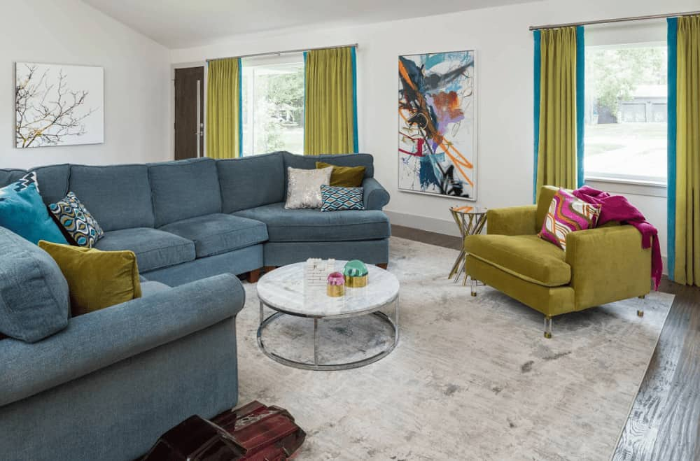 A moss green armchair matches the draperies covering the glazed windows that bring natural light in. This room showcases a blue sectional sofa and round coffee table over a distressed area rug.