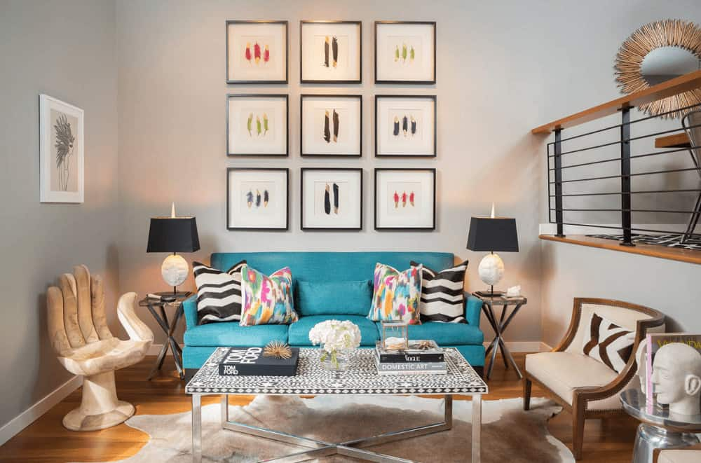 A feather art gallery sets a gorgeous backdrop to the blue sectional sofa accented with multi-colored and black and white pillows. It is accompanied by hand and beige chairs along with a metal coffee table on a cowhide rug.