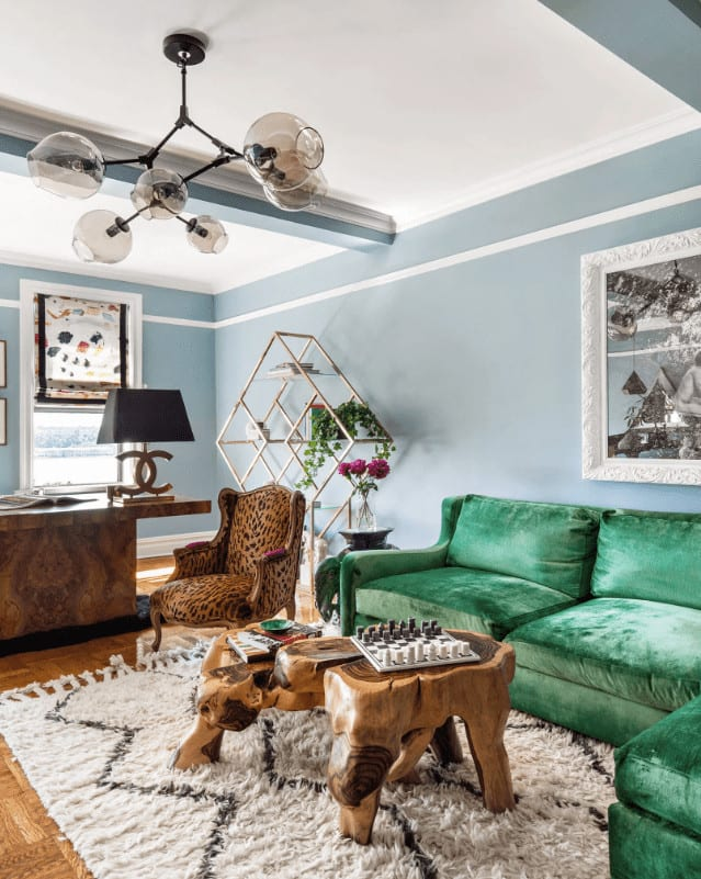 Eclectic living room painted in sky blue that's contrasted by green velvet sectional over a beige shaggy rug. It is accompanied by a leopard wingback chair and stump coffee table that's lighted by a glass globe chandelier.