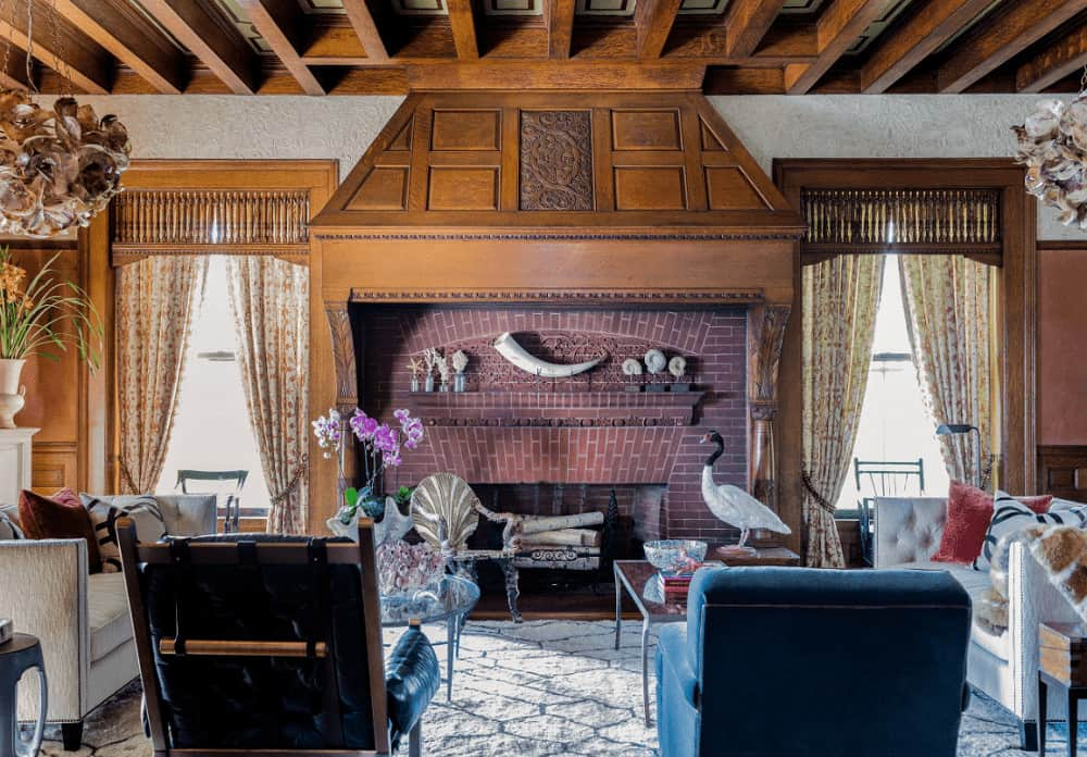 A pair of blue armchairs face the glass top coffee tables and fireplace clad in red bricks. It is flanked by wooden framed windows dressed in floral draperies.