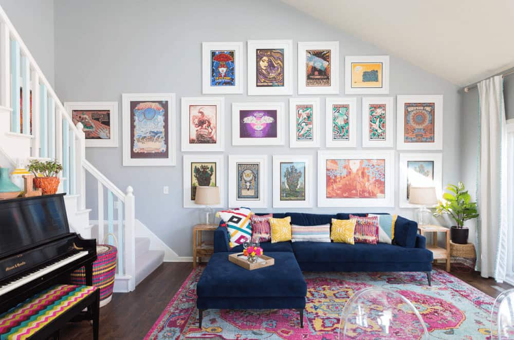 This living area is designed with an eclectic art gallery mounted above the blue L-shaped sofa. It has glass table lamps and a pink area rug that lays on the hardwood flooring.