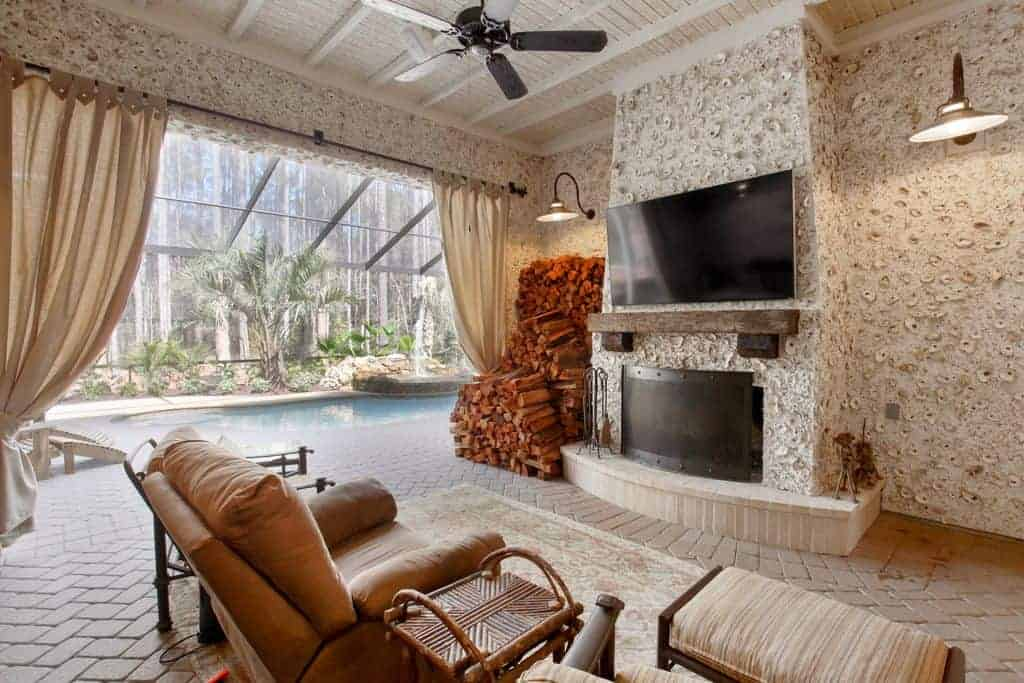 Airy living room with white textured walls and tiled flooring arranged in herringbone pattern. It has a wall mount TV above the fireplace and a sparkling pool on the side accented with green plants.
