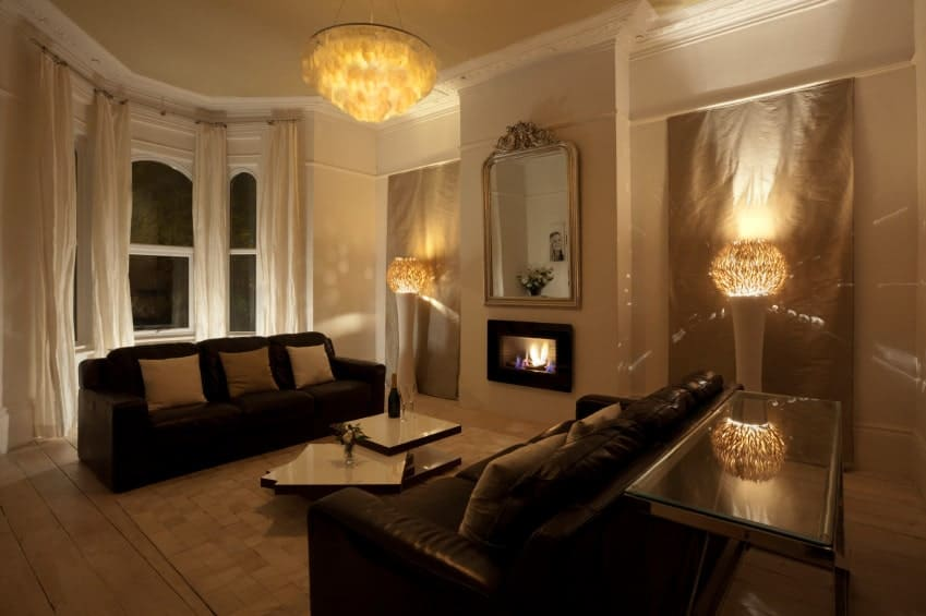 Ambient light from the unique floor lamps and chandelier create a warm and cozy feel in this living room with black leather sofas and modular coffee table facing the fireplace and mirror.