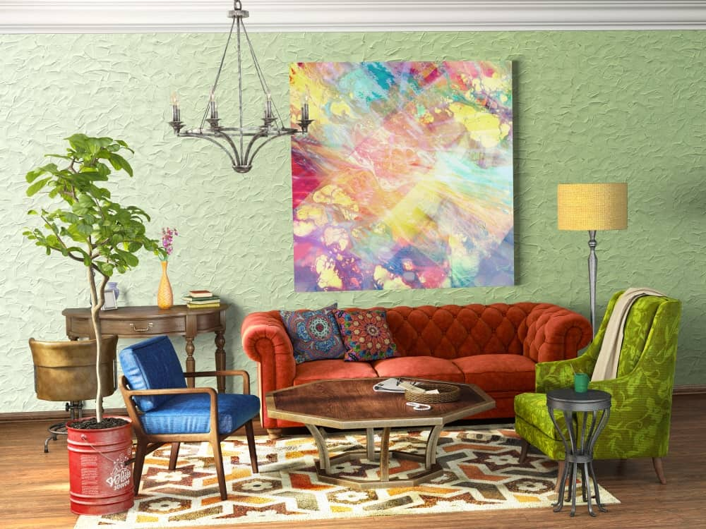 A chrome candle chandelier illuminates this living room offering multi-colored seats and artwork mounted on the mint green textured wall. There's a wooden desk on the side paired with a round back swivel chair.