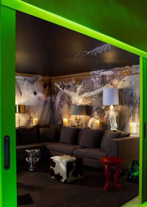 A green sliding door opens to this eclectic living room offering various styled stools and a brown sectional sofa against the wall mural blending in with the carpet flooring.