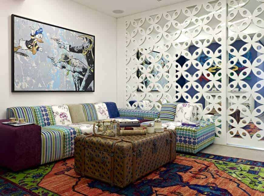 This living room boasts a stylish mirrored wall and an L-shaped sofa with large wall art on top paired with a chest coffee table over a brightly colored rug.