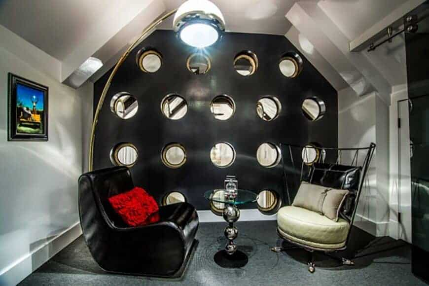 The small living room showcases sleek chairs and a stylish glass top table lighted by an arched floor lamp. It has a vaulted ceiling and black accent wall with large round holes.