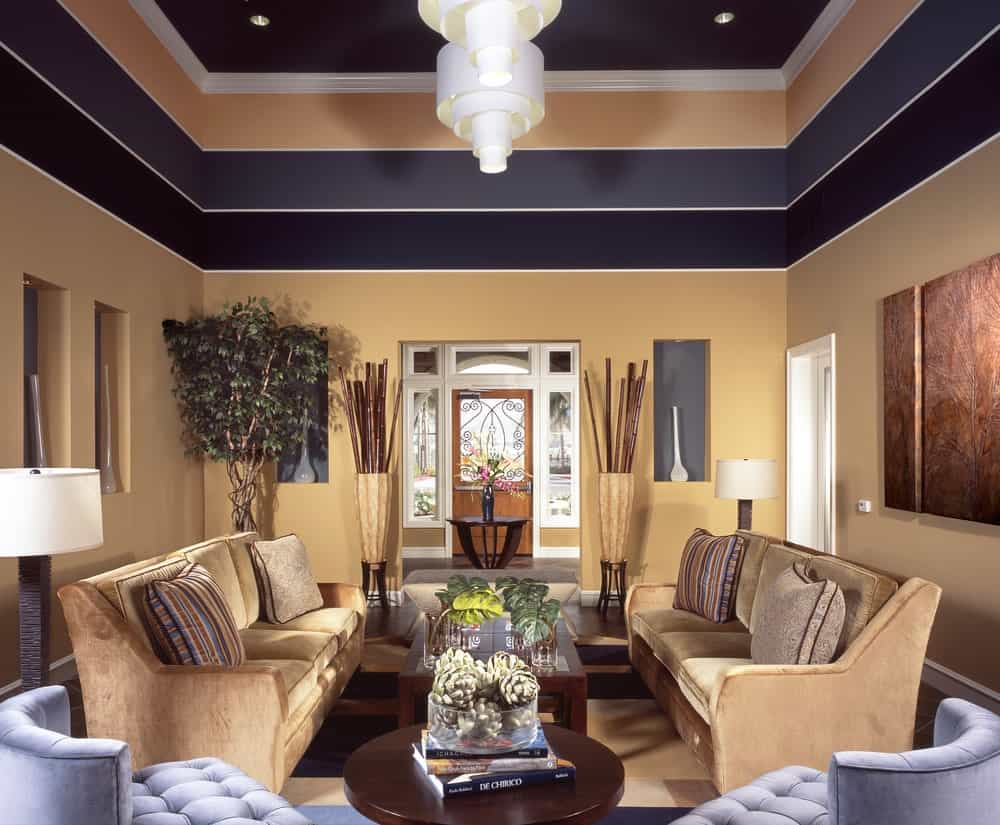 Sophisticated living room with inset wall niches and multi-colored upper walls creating an illusion of layered tray ceiling. It has velvet sectionals and gray tufted chairs with wooden coffee tables in the middle lighted by white pendants.
