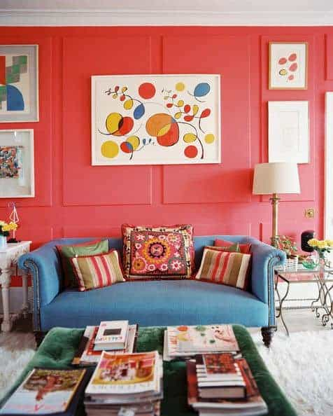 Pink living room with a blue sofa and green tufted ottoman topped with books. It has carpet flooring and wainscoted walls mounted with lovely artworks.