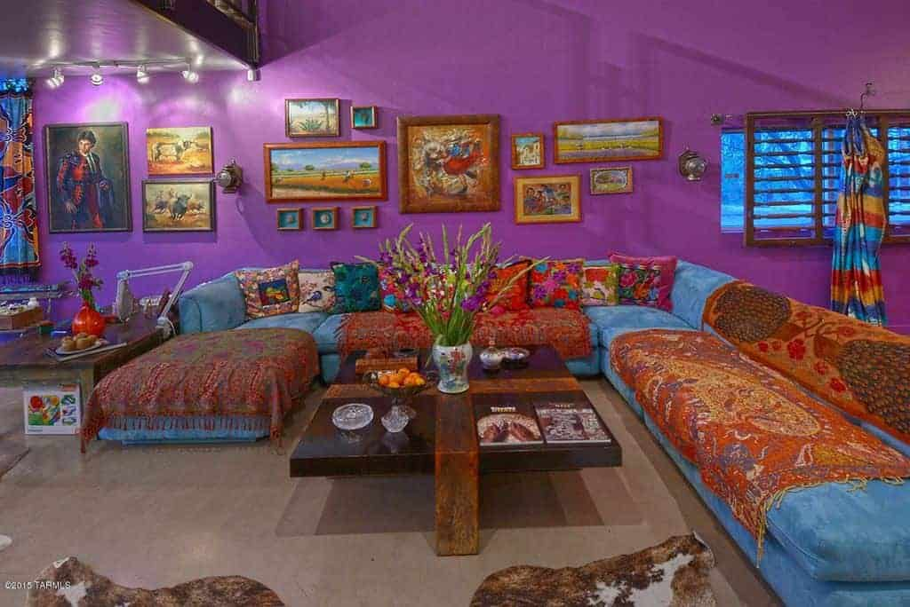 Purple living room designed with gallery frames mounted above the blue velvet sofa. There's a dark wood coffee table in the middle topped with <a class=